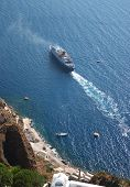 A pleasure cruise ship leaving the port of Fira on Santorini, Greece, seen from cliffs 1,000 feet above.