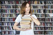 Woman Model College Student Working At Library Holds Bunch Of Books In Hands, Looking Smart. Bookshe poster