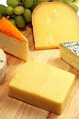 A well-supplied gourmet cheeseboard with cheddar to the fore.