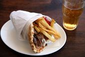 A souvlaki pitta gyros, the standard Greek kebab or meat wrap, with fries, yoghourt and salad, and a beer.