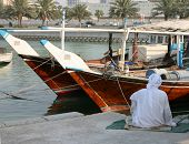 A fisherman sits beside his dhow in Doha, Qatar, during the heat of the day. September 2008 (Ramadan