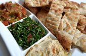 Three Middle Eastern dips in a mezze bowl with Turkish flat bread. Hummus is in the foreground, tabo