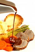 A meal of roast beef with carrots, Yorkshire puddings, potatoes and asparagus, with gravy being pour