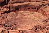An aerial view of the Roman-era amphitheater carved into the pink sandstone at Petra, Jordan. The building facades cut into the rock behind are ancient graves.