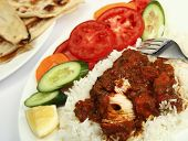 a plate of chicken tikka masala, served with white rice, a side salad and flat chapatti or naan brea