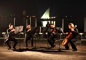 DOHA, QATAR - JANUARY 8: A string quartet performs against the backdrop of the Arabian Gulf and an A