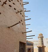 An Arabian pigeon house in front of an ornate mosque and minaret in Katara cultural village, Doha, Qatar, Arabia