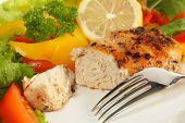 A saut�©ed peppered lemon-marinaded chicken breast served with a slice of lemon and salad vegetabl