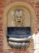 Wall fountain with gargoil spitting water