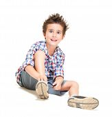 stock photo of fidget  - Naughty hairy little boy in shorts and shirt putting on shoes isolated on white - JPG