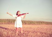 Young Woman Holding Violin And Bow Outdoors. Split Toning.