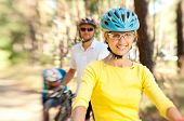 Family On Bikes In The Sunny Forest
