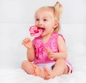 two year old blond girl eating a candy in bed at home