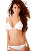 Sexy curvy young brunette woman with large breasts posing in a white bikini  three quarter isolated studio portrait