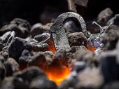 image of blacksmith shop  - a blacksmith is molding a piece of iron in a bracer - JPG