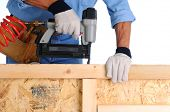 Closeup of a construction worker with a nail gun working on a wall he is building.