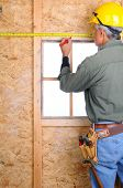 Closeup of a construction worker with a measuring tape marking a point on the wall he is building.