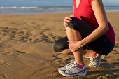 foto of injury  - Female runner clutching her shin because of a running injury and inflammation - JPG