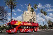 Sevilla, España - 16 de mayo: A City Sightseeing tour bus en la Torre del Oro el 16 de mayo de 2013 en Sevilla,