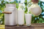 stock photo of milk glass  - Pouring milk in the glass on the background of nature - JPG