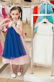 Beautiful girl tries on a blue dress in the store children clothes
