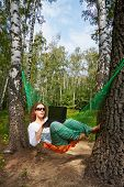 stock photo of birchwood  - Young barefooted woman in dark sunglasses lies in hammock at birchwood and works on notebook - JPG