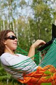 Young smiling woman in dark sunglasses lies in hammock outdoors and works on notebook