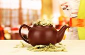 Dried herbs in teapot on wooden table, on bright background. Conceptual photo of herbal tea.