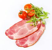two sliced of pork neck with cherry tomatoes, thyme and spring onion