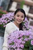 stock photo of petunia  - Thai Girl With Purple Petunia Flowers  - JPG