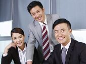 picture of coworkers  - a team of asian business people looking at camera and smiling.