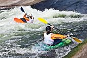 image of kayak  - two active kayakers are rolling and surfing in rough water - JPG