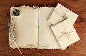 Open old book, letters and compass on wooden background