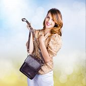 stock photo of sling bag  - Cute young retro fashion model holding leather clutch bag with hand to chest - JPG