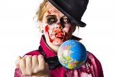 stock photo of unnatural  - Beaten and bloody zombie woman holding a globe stabbed with a knife - JPG