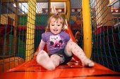 stock photo of indoor games  - Little girl having fun on a slide in an indoor activity centre - JPG