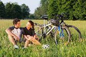 Happy Young Sportive Couple Sitting On Grass Besides Bicycles
