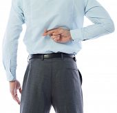 Businessman crossing fingers behind his back on white background