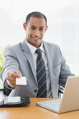 foto of half-dressed  - Smiling well dressed young man handing over his business card in front of laptop at office desk - JPG