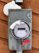 stock photo of hydro-electric  - A Hydro Electric Smart Meter covered with snow display $ dollar signs on the readout.