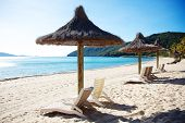 stock photo of deserted island  - beach lounge chairs under large umbrellas - JPG