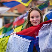 Young girl and Buddhist prayer flags flying in the Buddhist monastery.