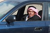 EGYPT - FEBRUARY 2: Arab man with red keffiyah driving his car on February 2, 2011 in Dahab, Egypt. Red and white keffiyahs is the pattern used by the majority of the Arab world.