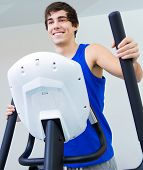 stock photo of elliptical  - Portrait of young man with elliptic machine in the gym - JPG