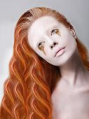Artistic Red Hair Woman With Painted Face And Creative Makeup