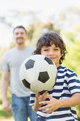 Portrait of a father and son playing football in the park
