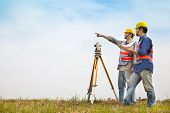 stock photo of theodolite  - Surveyor engineer making measure with partner on the field - JPG