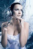 Glamour and bizarre portrait of young and beautiful woman smoking the electronic cigarette and listening to the music over creative winter background