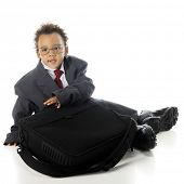 An adorable preschooler in an oversized business suit and his dad's dress shoes, getting ready to open his computer.  On a white background.