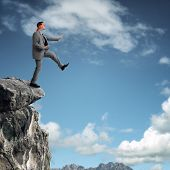 Businessman in a blindfold stepping off a cliff ledge concept for risk, challenge, conquering advers